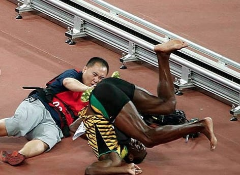Usain Bolt is floored by cameraman at World Championships in Beijing VIDEO